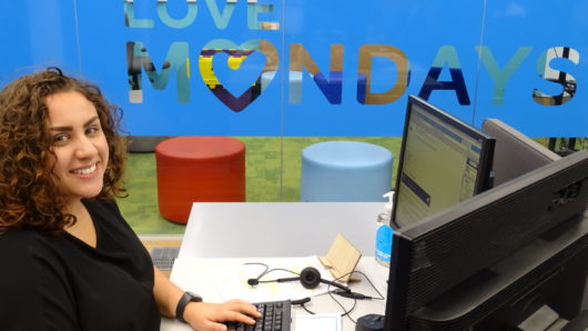 Manchester office - female consultant in reed specialist recruitment office in front of love mondays sign
