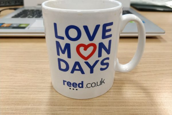 reed online jobs - reed.co.uk mug on desk with Love Mondays logo